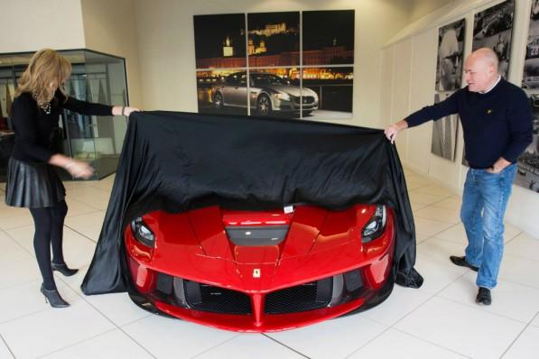 Paul Bailey and his wife Selena remove cover on their Ferrari LaFerrari